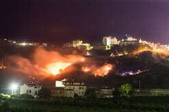 Corigliano Calabro, the ancient village of Corigliano threatened by a vast fire near the houses in the night.